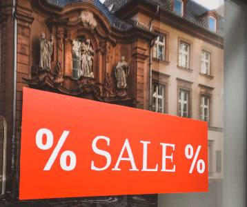 % sale sign on a glass window with reflections of neighbouring buildings